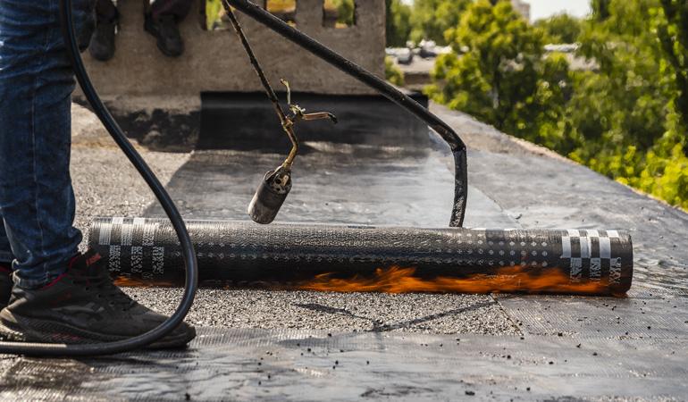 Pose de rouleaux bitumeux sur une toiture ancienne